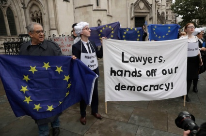 "Supporters of the pro-democracy group ""Invoke Article 50 Now!"" hold a banner as pro-EU membership supporters hold EU flags on the first day of Gina Miller's, a founder of investment management group SCM Private, lawsuit at the High Court, in London, Thursday, Oct. 13, 2016. The financial entrepreneur's landmark lawsuit begins with a simple question: can Prime Minister Theresa May's government invoke Article 50 and trigger Britain's exit from the European Union without an act of Parliament? (AP Photo/Matt Dunham)"